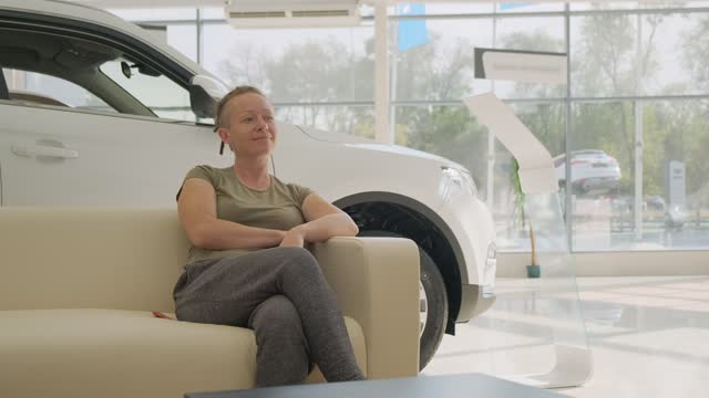 Happy woman in showroom in anticipation of deal sits on couch in front of new car.