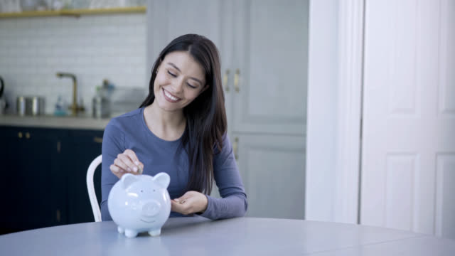 Happy woman inserting coins into her piggy bank