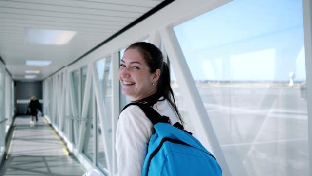 happy woman is going on empty telescopic gangway to the airplane. - wchodzić na pokład filmów i materiałów b-roll