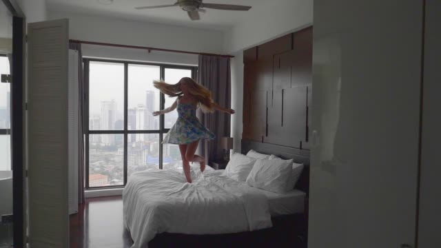 Happy Woman Jumping on the Bed