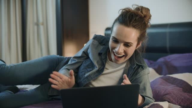 glückliche frau lacht mit laptop zu hause aufgeregte person klatscht hand - lotto stock-videos und b-roll-filmmaterial