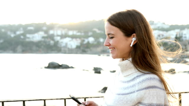 Happy woman listening to music walking and dancing