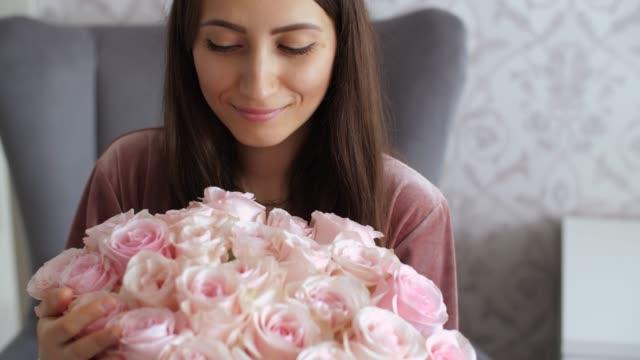 vidéos et rushes de regard heureux de femme sur le bouquet des roses - composition florale