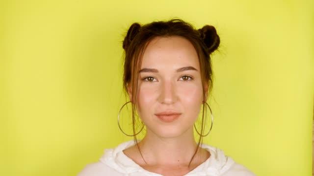 glückliche frau schaut in die kamera und lächelt über isolierten gelben hintergrund - farbiger hintergrund stock-videos und b-roll-filmmaterial