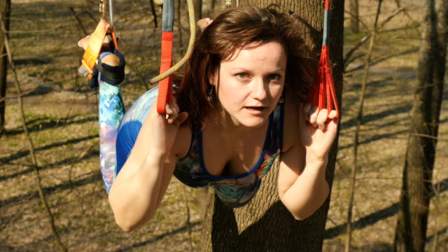 Happy woman makes physical exercises on the ropes outdoors Young woman practicing aerogravity in the park. The woman makes physical exercises on the ropes on tree. Flexible female hanging on the ropes and stretching her body and muscles. She's moving slowly and accuracy. arthropod stock videos & royalty-free footage