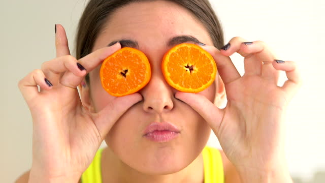 Happy woman making sillyfaces with fruit over eyes video