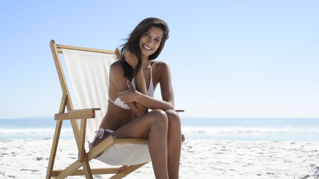 Happy woman on deckchair at beach Beautiful woman sitting on a deck chair at the beach and looking at camera. Young tanned woman in white bikini enjoying the summer with copy space. Hispanic woman subathing at seaside and laughing. Relaxed beautiful girl enjoying the sea. swimwear stock videos & royalty-free footage