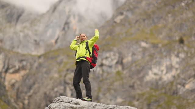 stockvideo's en b-roll-footage met happy woman on mountaintop - handen op de heupen