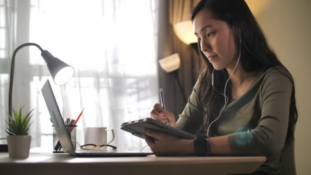 glückliche frau online-studentin trägt kopfhörer auf video anruf, studieren online zu hause - webinar stock-videos und b-roll-filmmaterial