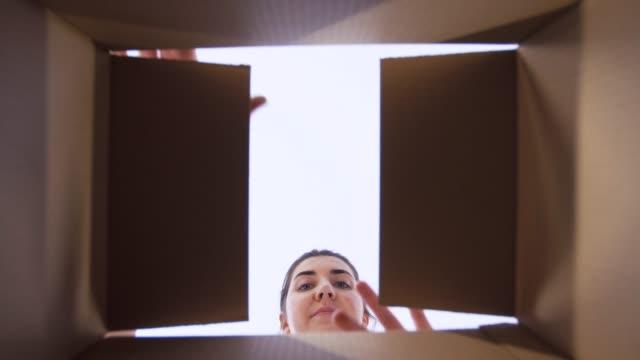 glückliche frau öffnet paket oder geschenkbox - innerhalb stock-videos und b-roll-filmmaterial