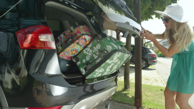SLOW MOTION: Happy woman opens the trunk of her black SUV and luggage falls out. SLOW MOTION, CLOSE UP, LENS FLARE: Happy Caucasian woman opens the trunk of her black SUV and luggage falls out. Funny shot of girl overpacking her car with suitcases for her upcoming summer holiday. stuffed stock videos & royalty-free footage