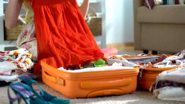 Happy woman packing a luggage for a new journey video