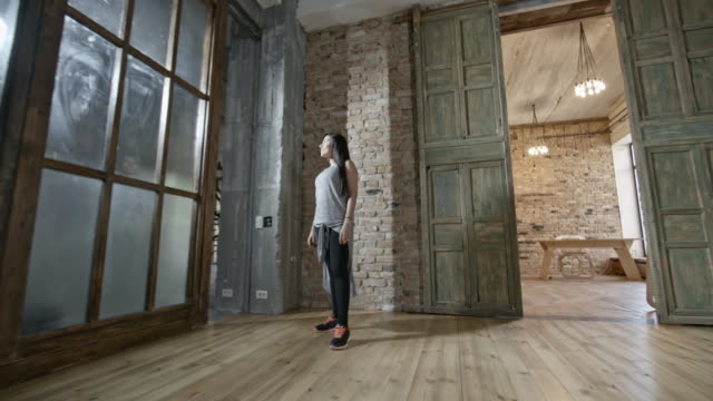 Happy Woman Posing in Loft Zoom in with PAN of cheerful Hispanic woman standing against brick wall in empty loft and looking at light loft apartment stock videos & royalty-free footage