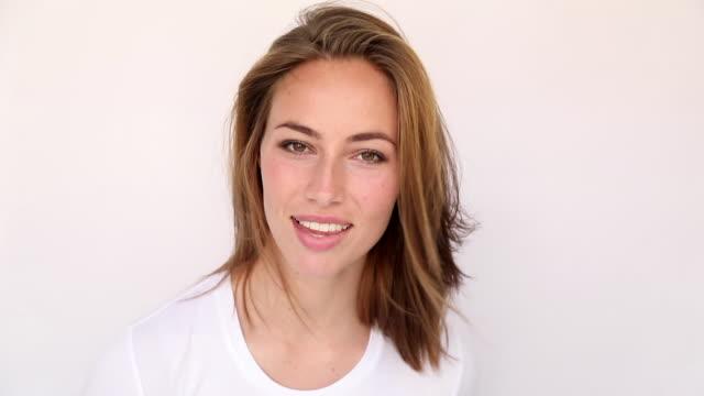 happy woman posing in studio - sfondo bianco video stock e b–roll