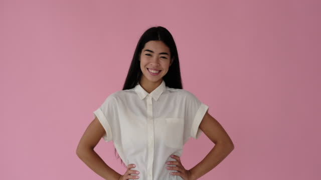 happy woman posing over pink background - mani sui fianchi video stock e b–roll
