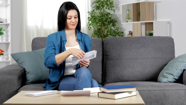happy woman reading a receipt at home - ricevere video stock e b–roll