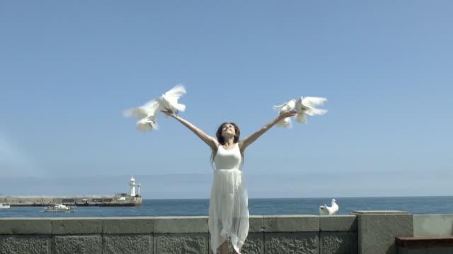 una donna felice piccioni rilascio - colomba video stock e b–roll