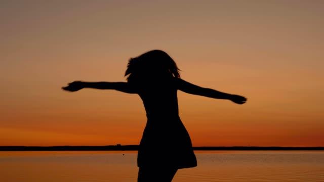 vídeos de stock e filmes b-roll de happy woman runs to the sunset to the beach raising her arms up and spinning - braços no ar