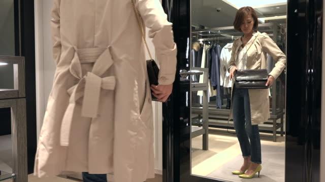 幸せな女革バッグのショッピングとミラーを見て - 小売り点の映像素材/bロール
