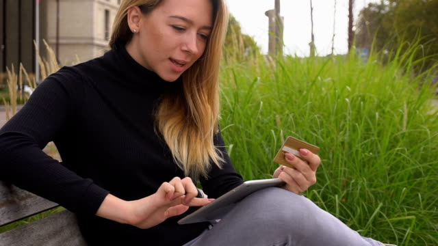 Happy woman shopping online with gold card in park by laptop Gladden female person purchasing goods in Internet by tablet and paying with gold card. Concept of online stores and buying things online. Pretty woman has blonde hair and wears black turtleneck sweater. gold card stock videos & royalty-free footage