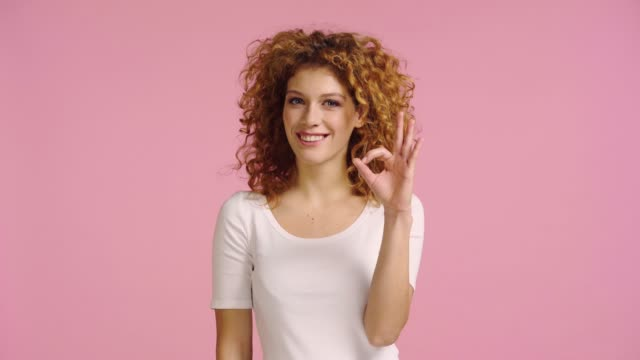 happy woman showing ok gesture and nodding isolated on pink