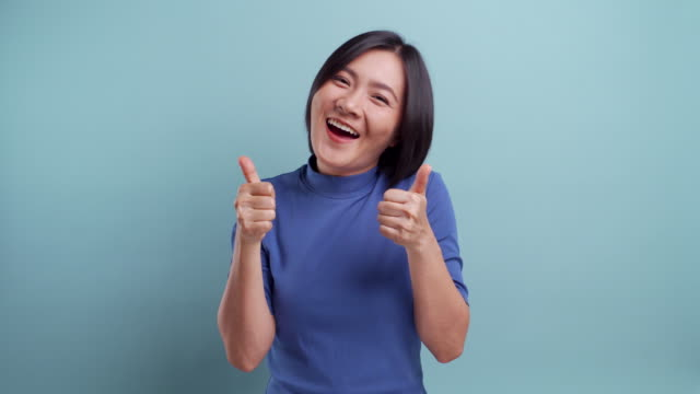 Happy woman showing thumb up isolated on blue background 4K video video