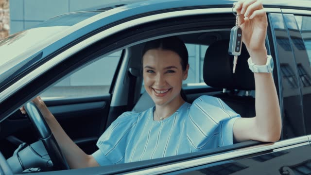 happy woman sitting in car on drivers place and showing car key happy woman sitting in car on drivers place and showing car key car key stock videos & royalty-free footage