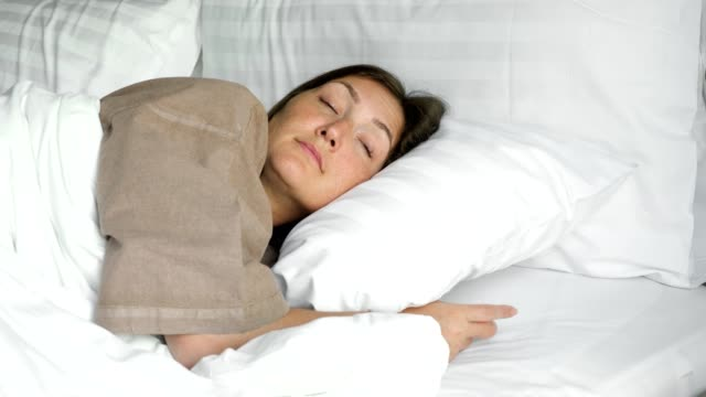 happy woman sleeps in bed with blanket and pillows in hotel