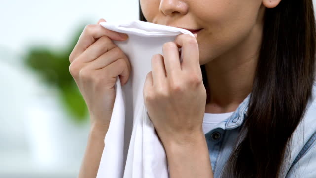 Happy woman smelling clean clothes aroma, enjoying good quality fabric softener