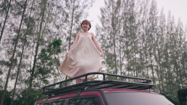 A happy woman spins around on a car with Beautiful nature stock video