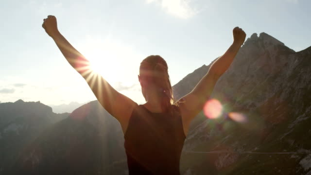 close up: happy woman standing on the edge of the mountain with hands raised - braccia alzate video stock e b–roll