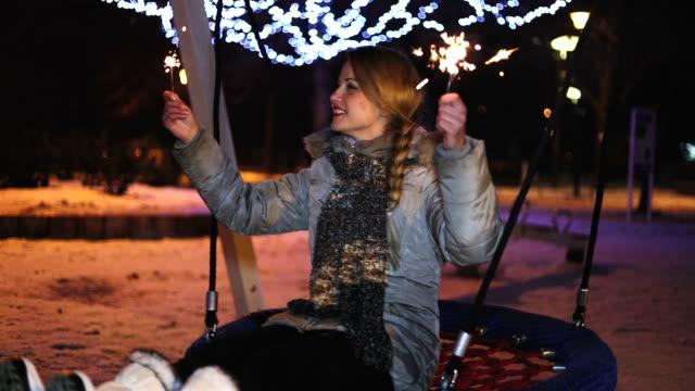 Happy woman swinging at winter night