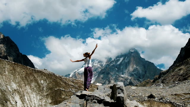 happy woman tourist jumping on a stone on a background of a snowy mountain in a hike. concept of achieving the goal, success and victory - pugno video stock e b–roll