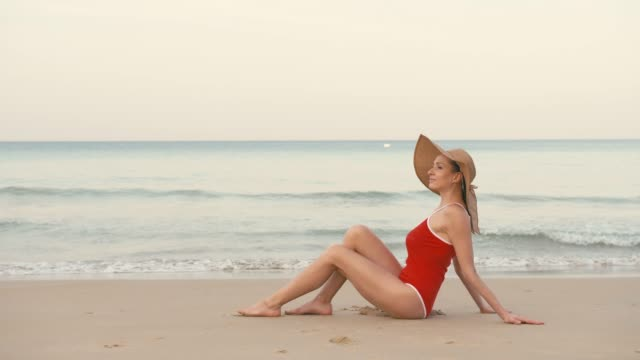 Happy woman traveler in red swimsuit and hat relaxing on a perfect beach Happy woman traveler in red swimsuit and hat relaxing on a perfect beach somewhere in Asia swimwear stock videos & royalty-free footage
