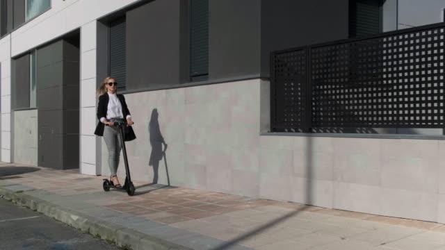 stockvideo's en b-roll-footage met gelukkige vrouw reist op elektrische scooter op de stoep - men blazer