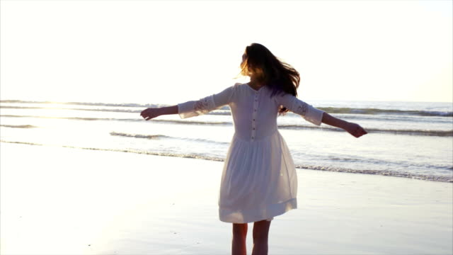Happy woman turning and twirling around on beach video