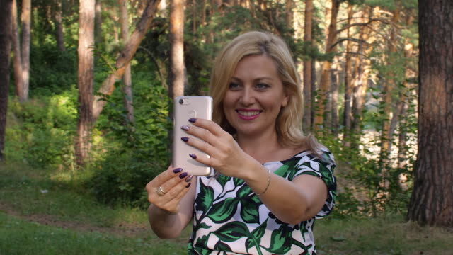 vídeos de stock e filmes b-roll de happy woman using mobile phone for video calling in summer park - amizade feminina