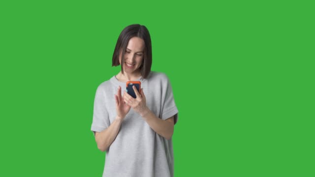 Happy woman using mobile phone over green background