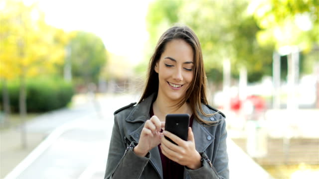 Happy woman walking and browsing on phone in a park Front view of a happy woman walking and browsing on smart phone in a park tapping stock videos & royalty-free footage