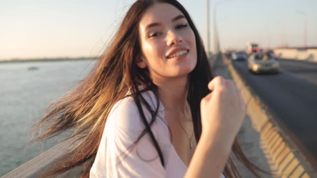 Happy woman walking on a bridge, make follow me gesture, slow motion video
