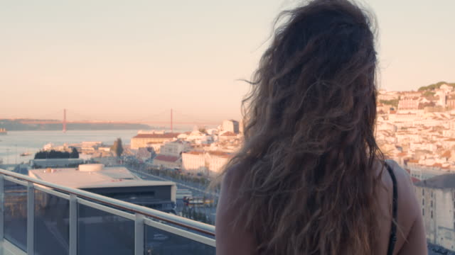 vídeos de stock e filmes b-roll de happy woman walking on the balcony with view on the city lisbon, portugal. back view of young lady against the background of lisbon - eletrico lisboa
