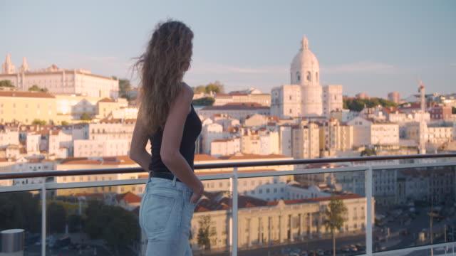 vídeos de stock e filmes b-roll de happy woman walking on the balcony with view on the city lisbon, portugal - eletrico lisboa