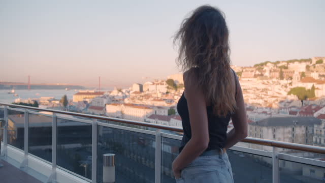 Happy woman walking on the balcony with view on the city Lisbon, Portugal Happy woman walking on the balcony with view on the city Lisbon, Portugal portugal stock videos & royalty-free footage
