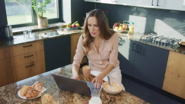lycklig kvinna tittar på video i köket. leende kvinnlig person som tittar på dator - looking inside inside cabinet bildbanksvideor och videomaterial från bakom kulisserna