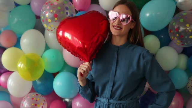 Happy woman with a heart-shaped balloon