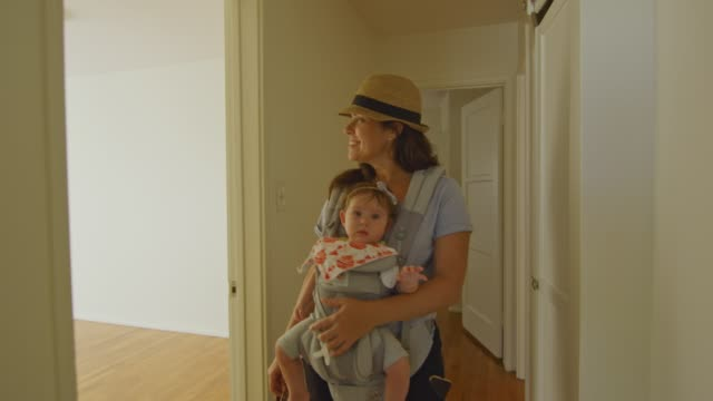 Happy woman with baby in carrier walking around an empty apartment video