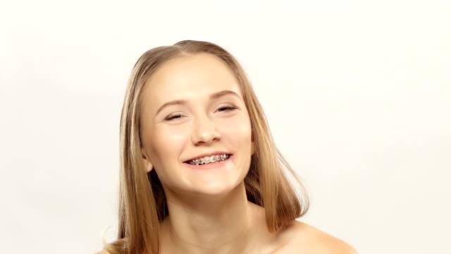 glückliche frau mit klammern auf zähne vor und lacht. weiß - verbogen stock-videos und b-roll-filmmaterial