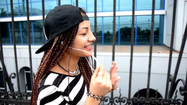 Happy woman with dreadlocks walking in headphones, talking by hands-free video