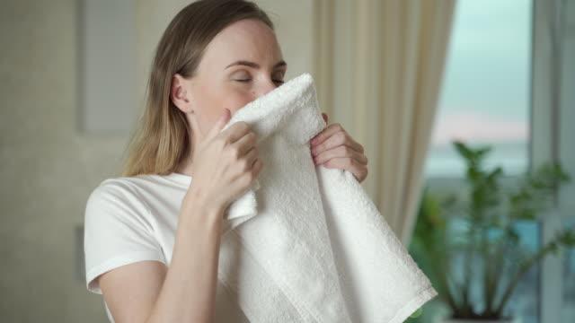 その新鮮な洗濯の香りを取ってリビングルームで洗濯を持つ幸せな女性 - 楽しい 洗濯点の映像素材/bロール