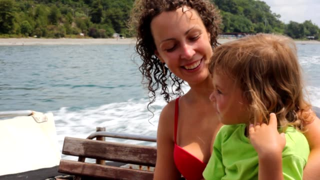 Happy woman with little girl sitting in going cutter video